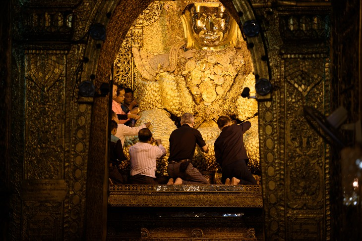Applying gold leaf to the Mahamuni Buddha figure